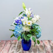 Photo of a blue, purple and white summer arrangement featuring blue hydrangea, white lilies and daisies in blue vase. This arrangement was crafted by Steve's Floral in Manhattan, KS.