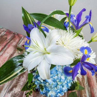 Close up of a white lily in a blue, purple and white summer arrangement featuring blue hydrangea, white lilies and daisies in blue vase. This arrangement was crafted by Steve's Floral in Manhattan, KS.