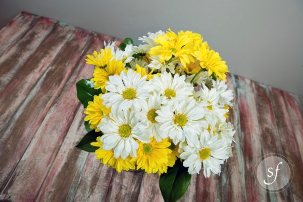 Top view of yellow, white daisies in bright, summery arrangement.