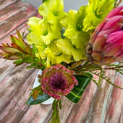 Warm tropical blooms in modern vase make the perfect arrangement for summer.