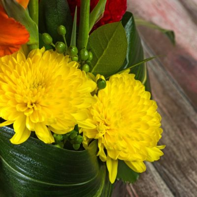 Yellow Chrysanthemums pop against aspidistra leaves in vibrant modern flower arrangement from Steve's Floral in Manhattan, KS.