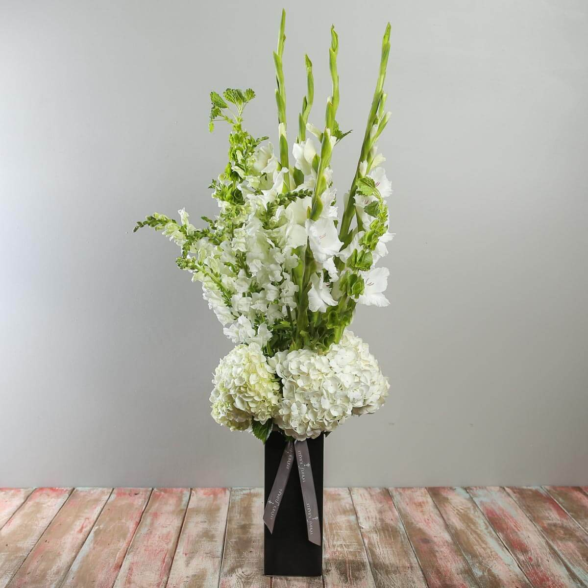 Serene garden sympathy steves floral statuesque white arrangement featuring hydrangeas gladioli snapdragons and bells of ireland in a izmirmasajfo
