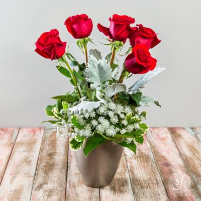 Bright red roses headline this striking modern arrangement with dusty miller, sprays of baby's breath, and summer greenery in a modern matte metallic vessel.