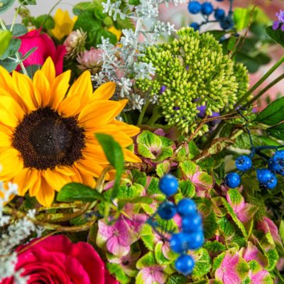 Close up of sunflower in a multi-colored summer arrangement featuring hydrangeas, roses, thistles, and more.