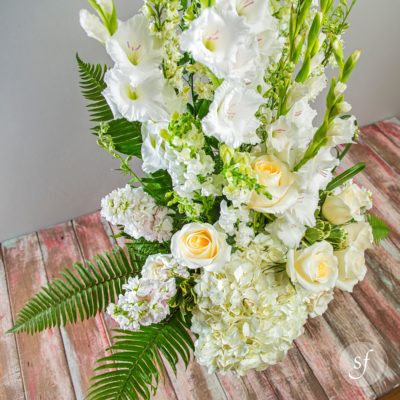Express sympathy with this large and elegant funeral arrangement featuring white gladioli, roses, hydrangea, and snapdragons in a black urn.