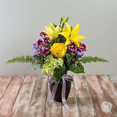 This bright summer arrangement features yellow roses, large stargazer lilies, purple gerbera daisies, light green hydrangea, fern leaves, and summer greens in a vibrant purple vessel.