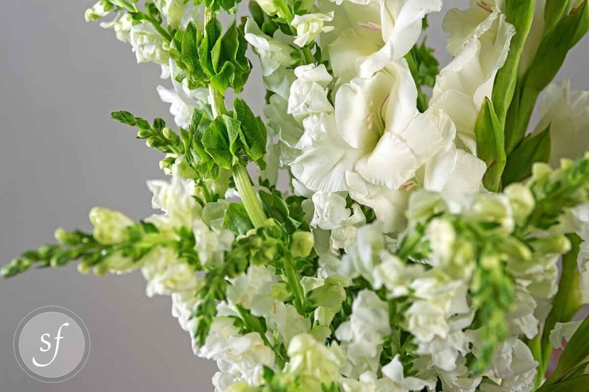 Serene garden sympathy steves floral close up of snap dragons and bells of ireland in stunning white funeral flower bouquet izmirmasajfo