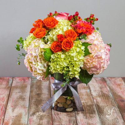 Happy summertime arrangement featuring green and blush hydrangea, orange roses, and variegated orange and blush double petaled roses in a clear base filled with decorative river rocks.