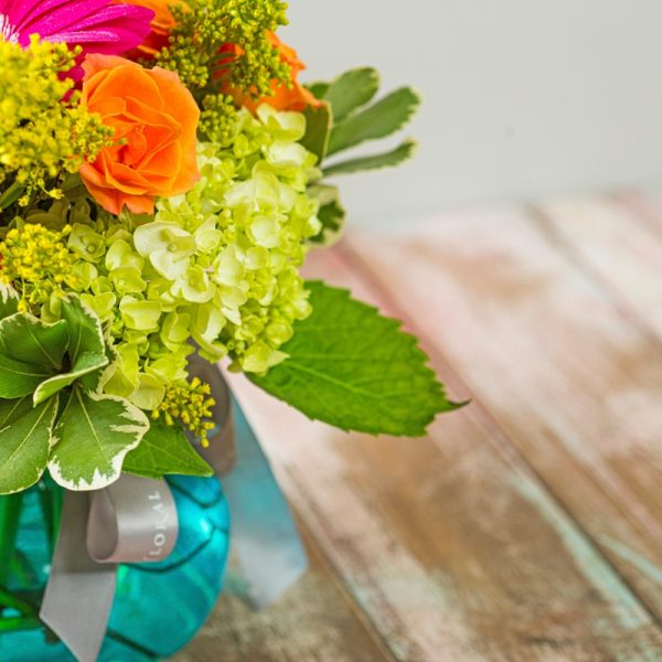Close up of green hydrangea in a bright and sunny arrangement that is perfect for summertime.