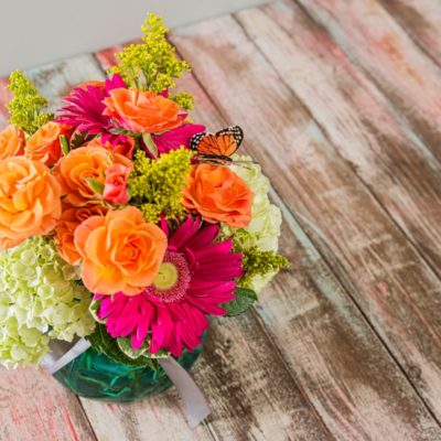 A monarch butterfly adorns this warm and bright arrangement which is perfect for summertime featuring orange spray roses, green hydrangea, and bright pink gerbera daisies in a bright, teal glass vase.