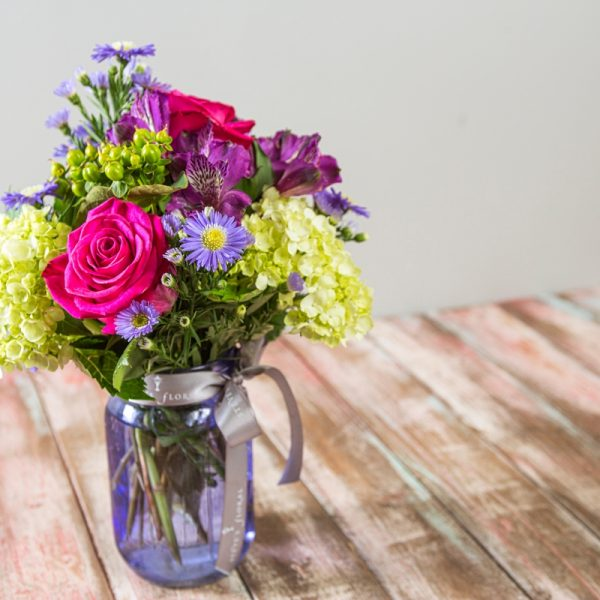 This vintage styled, jewel-toned summer arrangement in a lavender mason jar features bright pink roses, green hydrangea, purple aster, and plum alstroemeria.