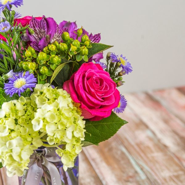 Side view of vintage styled jewel toned summer arrangement in lavender mason jar featuring bright pink roses, green hydrangea, purple aster, and plum alstroemeria.