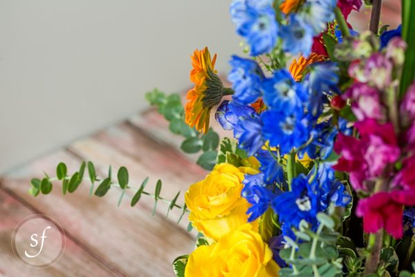 Close up of yellow roses in a jewel-toned arrangement in a shiny, square copper base features orange gerbera daisies, yellow roses, and blue delphinium.