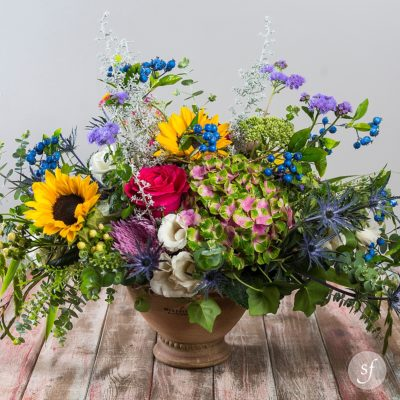 A ceramic vase overflows with colorful summer blooms including roses, hydrangea, sunflowers, and more.