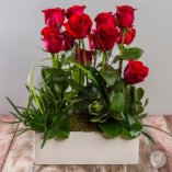This modern rose centerpiece is a beautiful and elegant gift. Perfect flowers for an anniversary or as a Valentine's Day gift, this romantic flower arrangement is sure to surprise your sweetie. Designed by Hildegaard Bembry, Steve's Floral's expert florist, this arrangement is available for same day flower delivery.