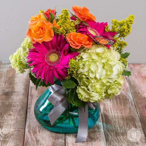 Sassy Breeze is a jewel toned summertime arrangement featuring hydrangea, gerbera daisies, and roses.