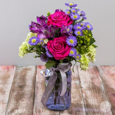 Vintage Garden is an affordable summertime arrangement featuring bright rose and purple aster in a glass lavender mason jar.