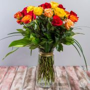 Eighteen long stemmed multi-hued roses grace an elegant glass vase. Designed by the florists at Steve's Floral, this arrangement is available for same day delivery.
