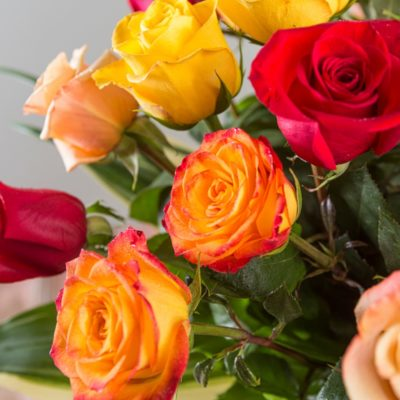 Close up of multi-colored red and yellow rose blossoms in an 18 stem bouquet.