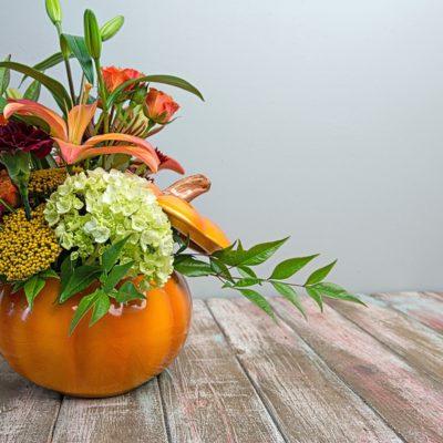 Festive, Autumnal flower arrangement in bright pumpkin container