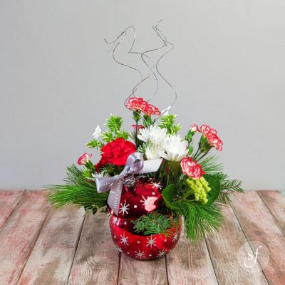 Red and white carnations and daisies headline this festive Christmas arrangement nestled in a sparkly Christmas ornament shaped vase.