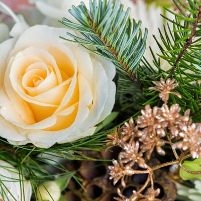 Funeral flowers in arrangement featuring white roses, pale green orchids, and seasonal greens.