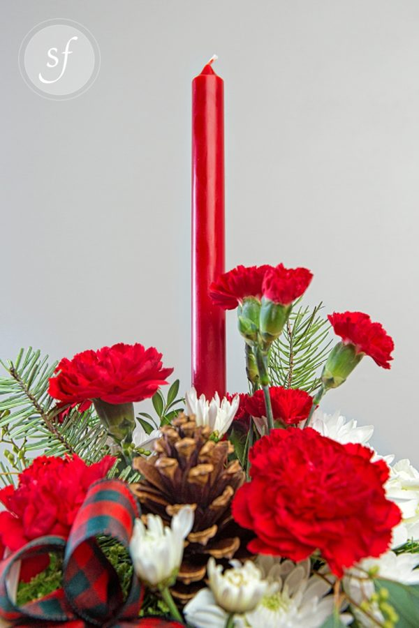 Festive Christmas flower arrangement featuring red, green checked ribbon, pine cones, and red and white carnations surrounding a lone, red tapered candle.