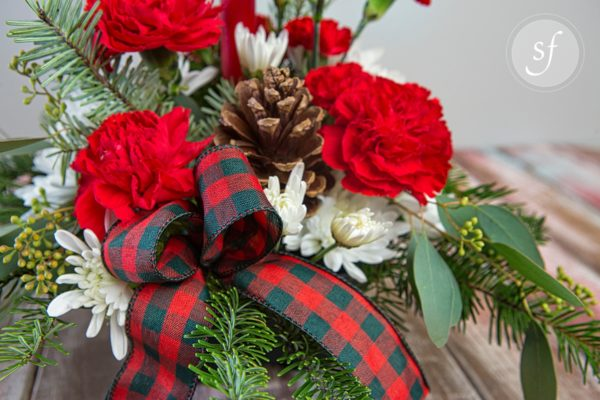 Festive Christmas flower arrangement featuring red, green checked ribbon, pine cones, and red and white carnations.