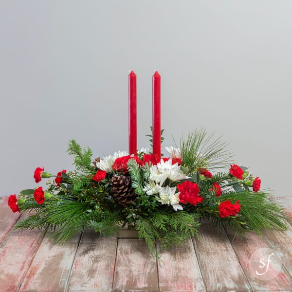 Christmas centerpiece featuring red and white carnations and mums and two tapered candles nestled in winter foliage.