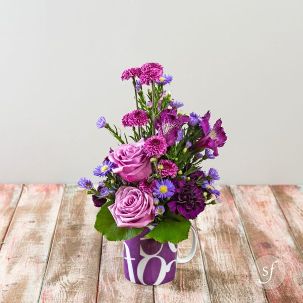 K-State Fan Floral Arrangement featuring lavender roses, plum carnations and alstroemeria, and purple aster in a Kansas State coffee mug.