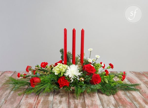 Red and white seasonal blooms surround three tapered red candles in this Christmas-y centerpiece.