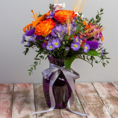 Ignition is a colorful fall arrangement featuring roses, lilies, purple aster, and wheat stalks in a deep purple vase. Ignition was designed by the professional florists at Steve's Floral in Manhattan, Kansas.