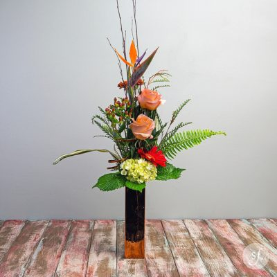 A bird of paradise rises above fall blooms in a shiny copper vase in this lovely fall arrangement designed by Steve's Floral in Manhattan, KS.