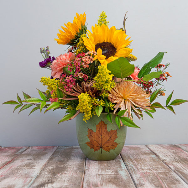 Sunflowers and fall greenery burst from a warm vase with a fall motif.