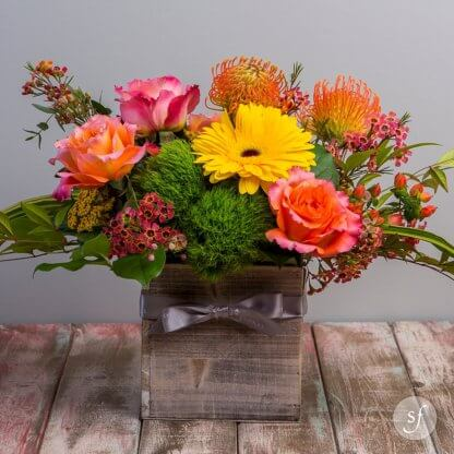 The Brighten Your Day arrangement is a sweet fall arrangement featuring colorful blooms in a rustic box base.