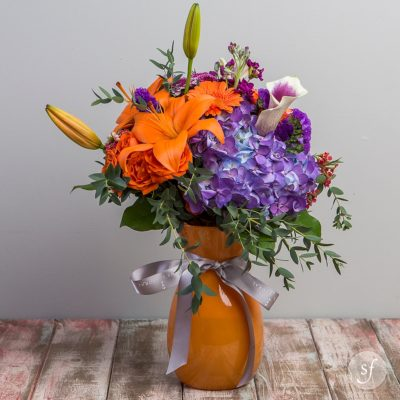 Vibrant oranges pop against elegant purple hues in this fall arrangement featuring lilies, gerbera daisies, and hydrangeas. Callas and lilies was designed by the professional florists at Steve's Floral in Manhattan, KS.