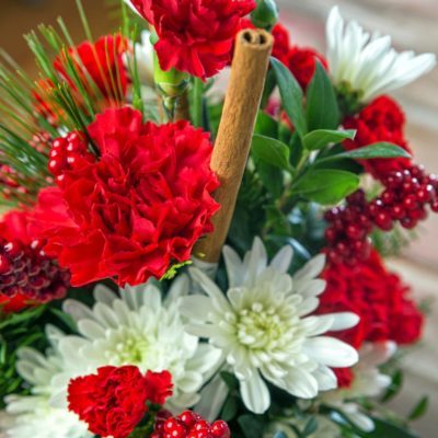Top view of blooms in a red and white winter arrangement featuring carnations, cinnamon sticks, evergreen branches, and Christmas berries.