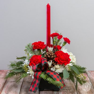 Glow is a petite Christmas arrangement that features red and white carnations, seasonal greens, and a red, tapered candle.