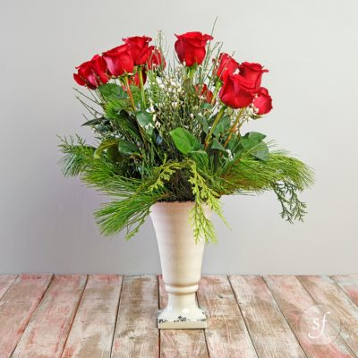 A dozen long-stemmed roses are surrounded by wintry greens in this cold-weather bouquet.