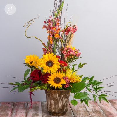 The Flint Hills Special is a towering arrangement featuring sunflowers and other bright fall blooms in a rustic basket.