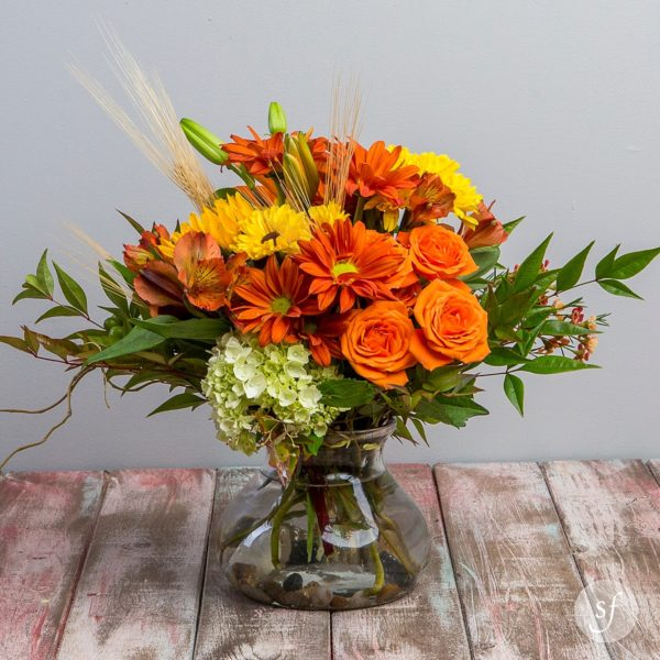 Orange Crush features classic autumn blooms accented with wheatgrass and foliage in a clear vase with river rocks.