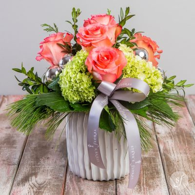 Serenity features soft pink roses accented with seasonal greenery in a textured white ceramic vase. Designed by the florists at Steve's Floral in downtown Manhattan, Kansas, it is a sweet and small arrangement.