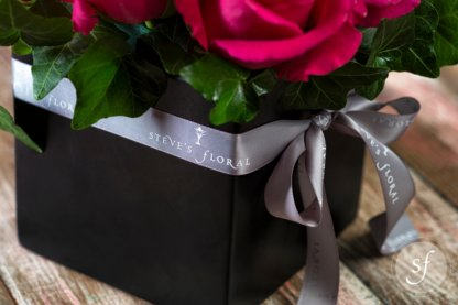 Close up of Steve's Floral grey ribbon wrapped around modern, square vase holding nine bright pink pave roses.