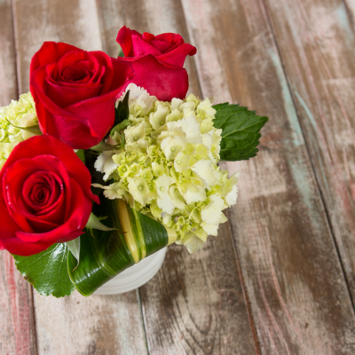 Three red roses accented with light colored hydrangeas and variegated green leaves headline this elegantly petite arrangement in textured ceramic vase.