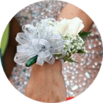 White rose silver ribbon corsage on extended wrist with prom dress in background.
