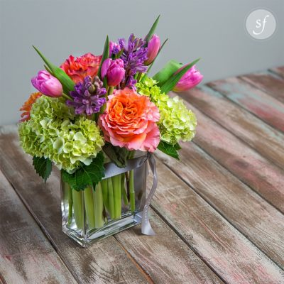 Bright springtime arrangement featuring bright blooms including tulips, roses and hydrangea. Perfect as an Easter centerpiece, this happy piece is sure to please.