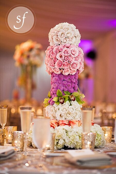 A tall, modern, pave-style wedding centerpiece features pastel roses, orchids, and hydrangeas. This stunning and bright piece is perfect for an elegant spring wedding.
