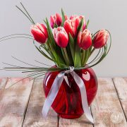 Perfect for Valentine's Day or as a warm, spring arrangement, Heart of Tulips features red tulips in a red glass vase.