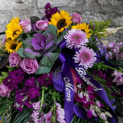 Purple cabbage, lavender roses, and bright sunflowers headline this bountiful casket spray for a beloved mother and wife in Manhattan, KS.