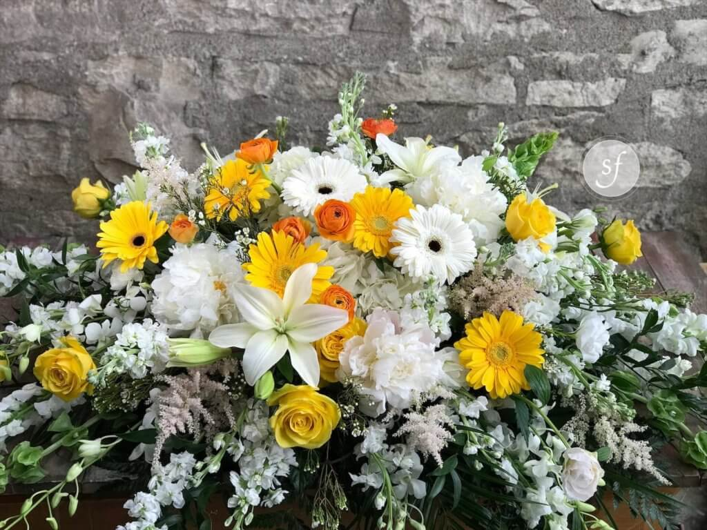 white and yellow casket spray